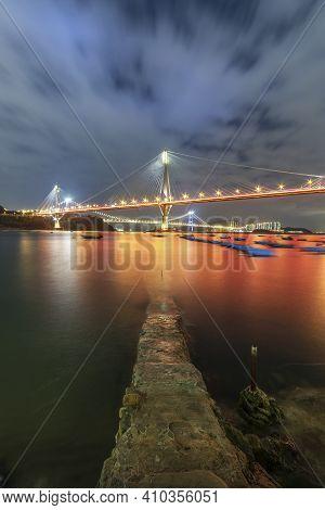 Idyllic Landscape Of Jetty And Bridge Of Hong Kong City At Night