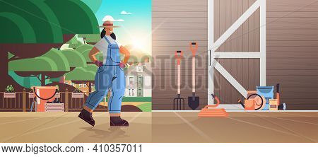 Girl Farmer In Uniform With Garden And Farm Tools Gardening Equipment Near Wooden Barn Doors Eco Far