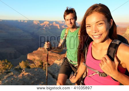 Couple hikers in Grand Canyon. Aspirational lifestyle image of happy young people hiking the South Rim trail of Grand Canyon. Multiethnic couple, Asian woman, Caucasian man.