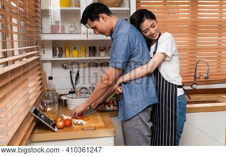 A Happy Young Couple Stands Together In The Kitchen At Home Preparing Together Dinner. Family Couple