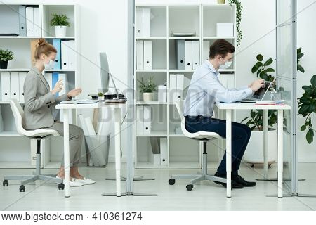 Young businessman in protective mask and formalwear wiping laptop display with wet wipe while his colleague spraying sanitizer on hands