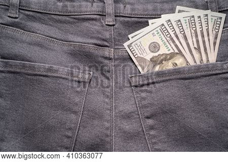 Cash In Your Pocket. A Hundred Dollar Bills Stuck Out Of The Back Pocket Of Grey Jeans. Money Saving