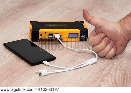 Hand With A Raised Thumb Next To A Smartphone Charging From A Plunging Powerbank