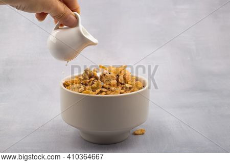 Bowl Of Corn Flakes Cereals And Spoon Isolated On Grey Background.