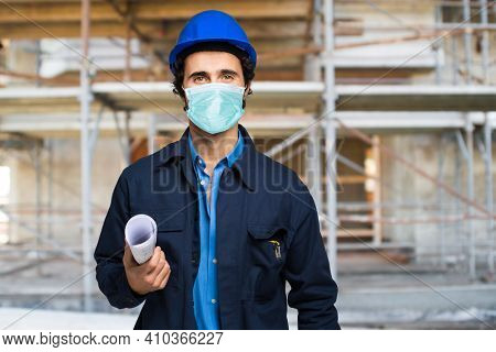 Masked architect portrait in a site plant, covid coronavirus construction site concept