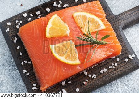 Salmon Fillet, Red Salted Fish On A Wooden Chopping Board. Lemon, Rosemary Spices.