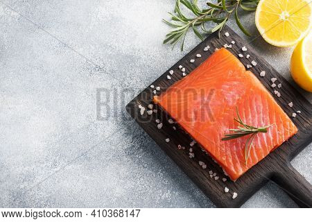 Salmon Fillet, Red Salted Fish On A Wooden Chopping Board. Lemon, Rosemary Spices. Copy Space.