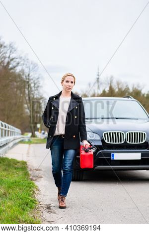 Woman out of fuel with car starting walking towards next gas station to get fuel