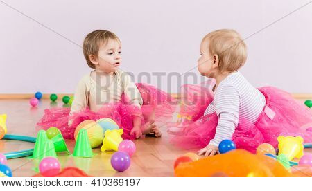 Two toddlers playing together with lots of toys