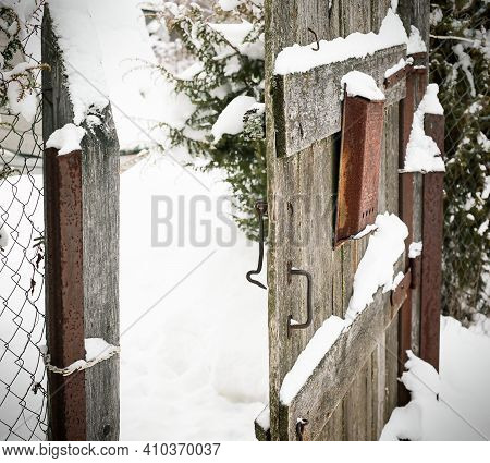 Old Wooden Gate In Fence Slightly Open. Winter Rural Landscape With Snowdrifts
