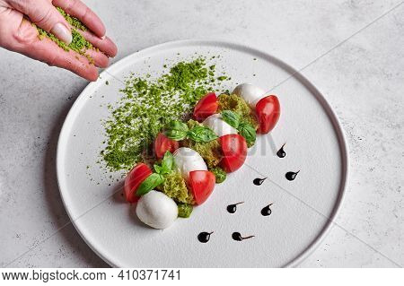 Womans Hands Sprinkled With Green Breadcrumbs To Delicious Italian Caprese Salad With Ripe Tomatoes,