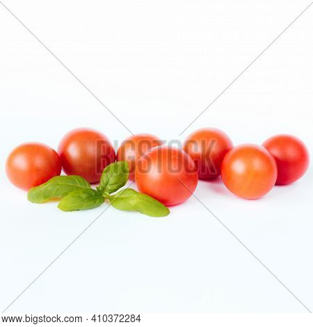 Red Cherry Tomatoes With Green Basil On A White Background
