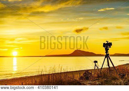Camera On Tripod Take Photo From Sunrise Over Sea. Montgo Mountain Massif Silhouette On Horizon. Vie