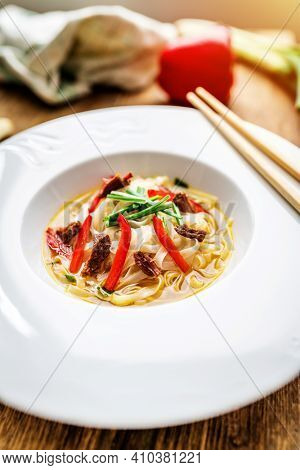 Vietnamese Soup Pho Bo With Asian Noodles And Beef Meat On Wooden Table
