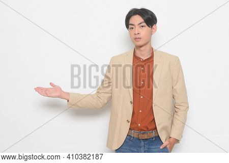 handsome young man in suit with jeans standing with hand in pocket, with hand palm posing on white background
