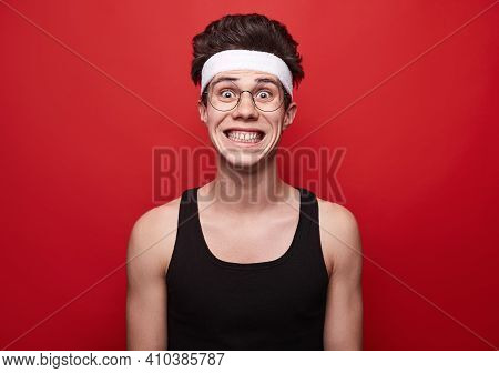 Crazy Excited Young Skinny Male In Sportive Wear And Glasses Making Funny Grimace And Looking At Cam