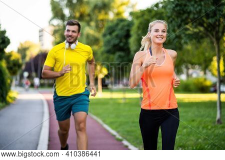 Young Couple Is Jogging On Running Track In Park.