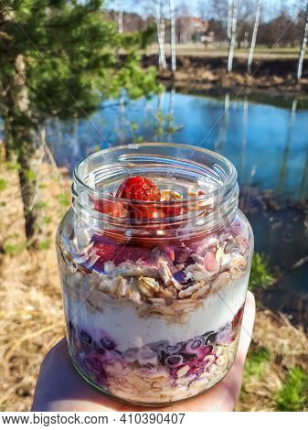 Healthy Breakfast Overnight Oats With Strawberries, Blueberries And Yoghurt In A Glass Jar With Beau