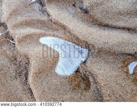 Water Frozen In The Shape Of Heart In Beach Sand. Macro Shot Of Ice Heart In Dune.