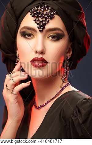 Close up portrait of a beautiful oriental woman with traditional make-up, black turban and jewelry on a black background. Make-up and cosmetics. Arabian beauty, fashion.