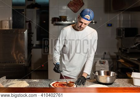 Pizza Man Adds Tomato To A Pizza In A Pizzeria Restaurant Kitchen