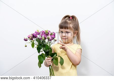 Little Girl In A Yellow Blouse With Faded Flowers.