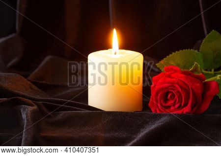 A Burning Candle And A Red Rose On A Black Cloth Background. The Concept Of Condolence And Religion.