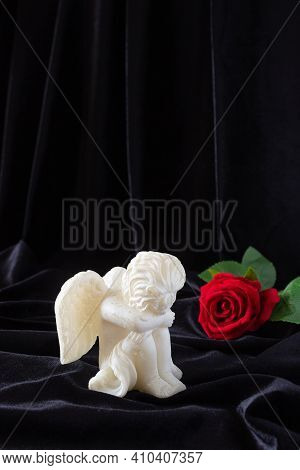 A Candle In The Form Of An Angel With Wings And A Red Rose On A Black Cloth Background. Free Space F