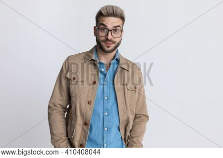 portrait of young casual man in denim shirt with eyeglasses holding hands in pockets and making funny frowning faces on grey background