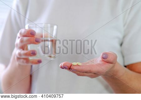 Close - Up Of A Pill In One Hand. The Woman Is Going To Wash Down The Medicine, Holding A Glass Of W