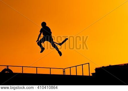 Unrecognizable Teenage Boy Silhouette Showing High Jump Tricks On Scooter Against Orange Sunsetwarm