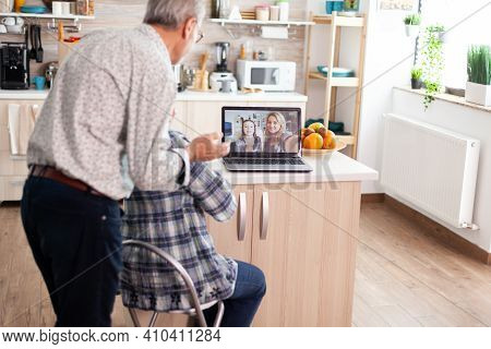 Senior Couple During Video Conference With Daughter In Kitchen Using Laptop. Enthusiastic Grandparen