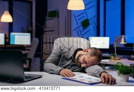 Tired Businessman Sleeping In His Workplace On Desk. Workaholic Employee Falling Asleep Because Of W