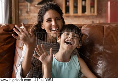 Portrait Of Happy Latino Mom And Daughter Talk On Webcam