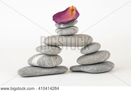 Balanced gray zen pebbles on white background. Zen stones. Spa and healthcare concept.