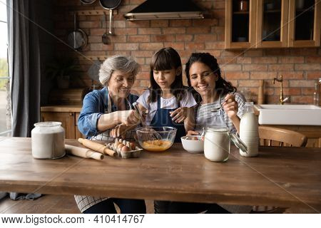 Happy Three Generations Of Women Cooking Together