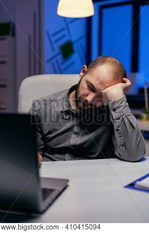 Businessman Sleeping In Company Office Due To Overworking. Workaholic Employee Falling Asleep Becaus