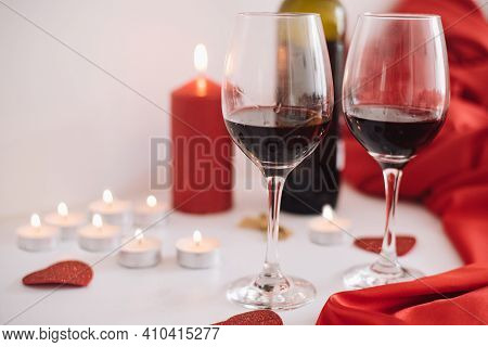 Two Glasses Of Red Wine Decorate By Candles And Red Fabric. Romantic, Unforgettable Evening With Ste