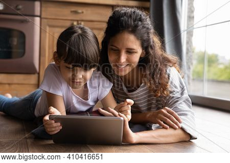 Happy Young Latino Mom And Daughter Use Tablet