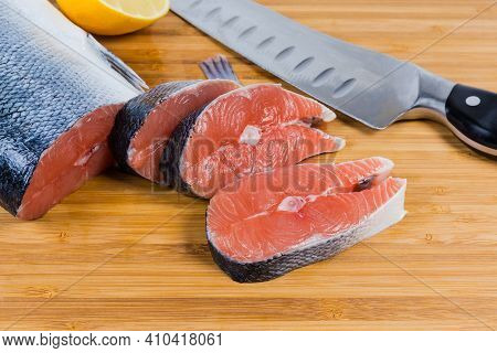 Uncooked Salmon Steaks And Not Sliced Piece Of Fish, Kitchen Knife On A Bamboo Cutting Board Close-u