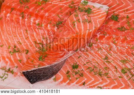 Slice Of Raw Chilled Uncooked Salmon Lies On Salmon Fillet Sprinkled With Chopped Dill Close-up