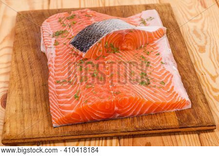 Slice Of Raw Chilled Uncooked Salmon On Skin Lies On Salmon Fillet Piece Sprinkled With Chopped Dill