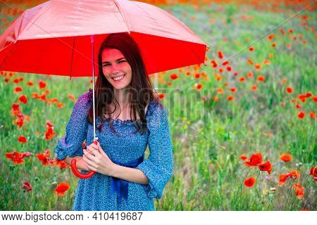 Young beautiful smiling woman wearing summer drees holding red umbrella in poppy field. Charming girl walks before the rain, nature outdoor