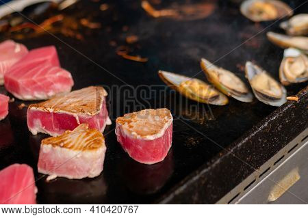 Process Of Cooking Mussels, Clams And Red Tuna Slices On Grill At Summer Local Food Market - Close U