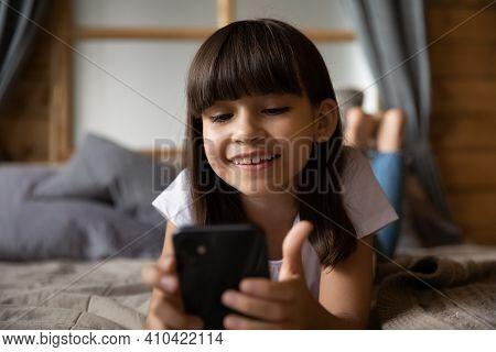 Smiling Small Latino Girl Use Modern Smartphone