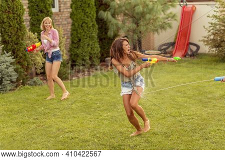 Group Of Young Friends Having Fun Spending Summer Day Outdoors, Playing With Squirt Guns, Splashing