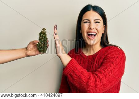 Beautiful brunette woman saying no to marijuana herb smiling and laughing hard out loud because funny crazy joke.