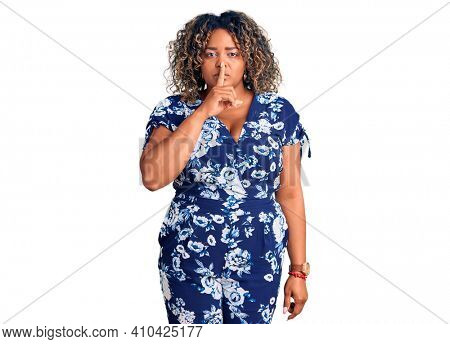Young african american plus size woman wearing casual clothes asking to be quiet with finger on lips. silence and secret concept.