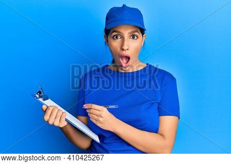 Beautiful brunette woman wearing courier uniform holding clipboard afraid and shocked with surprise and amazed expression, fear and excited face.