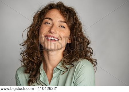Close up face of beautiful young woman smiling and looking at camera isolated on grey background. Portrait of beauty natural girl with copy space. Female student in casual standing against gray wall.